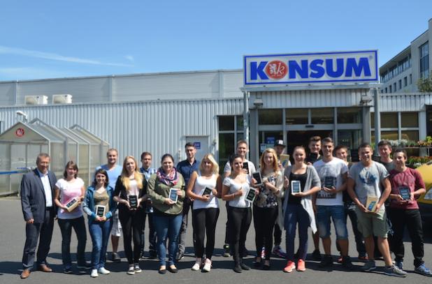 Roger Ulke, Vorstandsmitglied der KONSUM DRESDEN eG (l.), begrüßt die neuen Auszubildenden mit einem Tablet zur Prüfungsunterstützung. Bildquelle: Sarah Reichelt, Medienkontor Dresden GmbH
