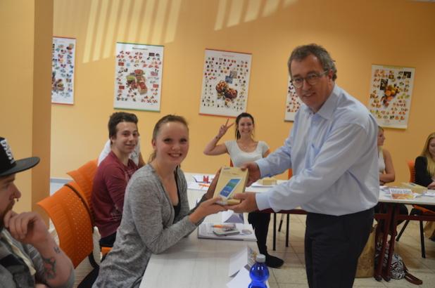 Roger Ulke, Vorstandsmitglied der KONSUM DRESDEN eG (l.), überreicht der Auszubildenden Julia Sicker (17) ihr Tablet. Bildquelle: Sarah Reichelt, Medienkontor Dresden GmbH