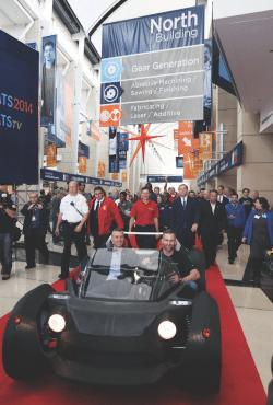 Strati, das weltweit erste 3D gedruckte Auto gedruckt, fährt auf der IMTS 2014 Hinter dem Steuer Jay Rogers, CEO und Mitgründer von Local Motors; der Beifahrer ist Douglas Woods, Präsident von AMT. - Quelle: IMTS Exhibitions Department