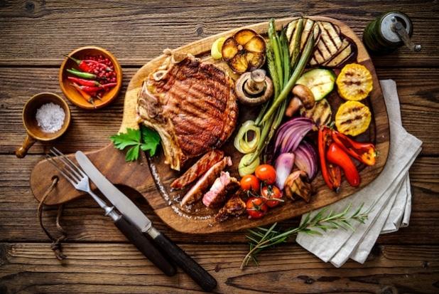 Gegrilltes Fleisch und Gemüse auf einem Holzbrett angerichtet